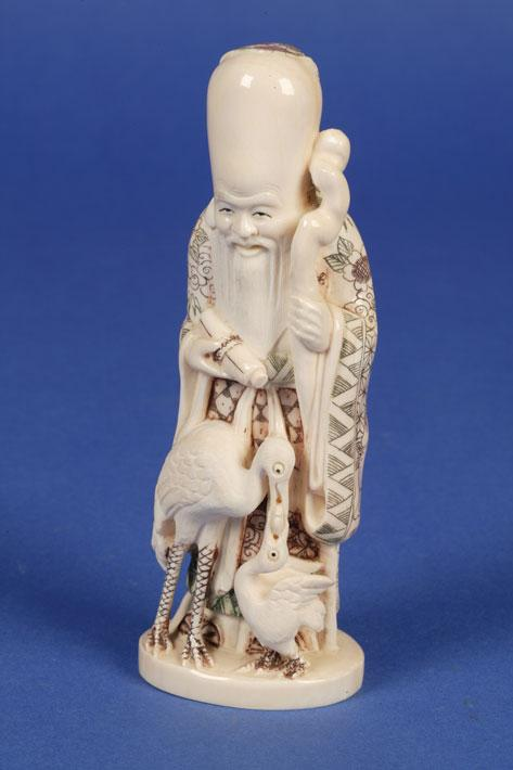 A JAPANESE IVORY FIGURE of an immortal holding