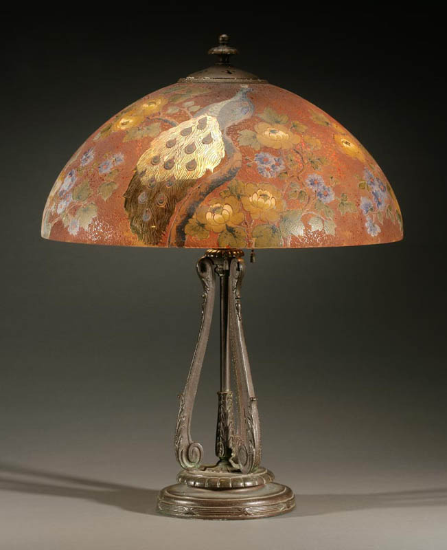 A Handel bronze chipped glass peacock lamp.