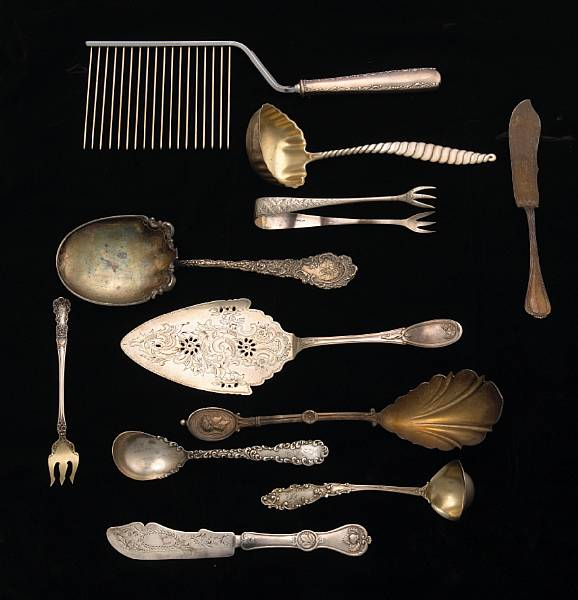A group of silver flatware service pieces