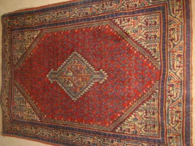 AN ANTIQUE NORTH WEST PERSIAN RUG, the red