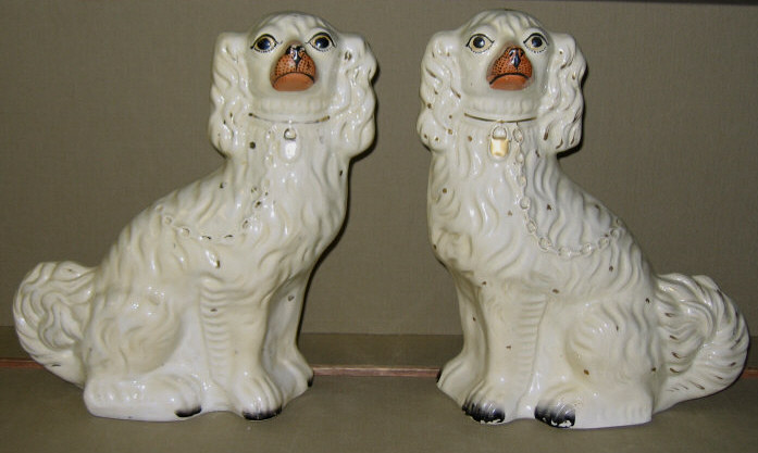 PAIR OF STAFFORDSHIRE POTTERY DOGS Each seated,